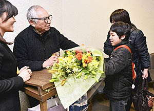 公演終了後、観客から花束を受ける倉本さん(左)