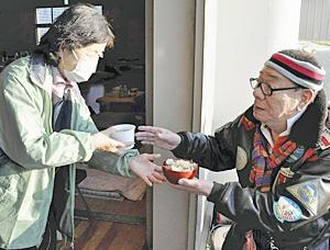 避難所で炊き出しを振る舞うケーシー高峰さん(右)=2011年3月、いわき市・泉公民館